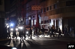 People cross a street during a power blackout in Caracas, Venezuela, March 7, 2019.