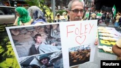 A man holds up a sign in memory of U.S. journalist James Foley during a protest against the Assad regime in Syria in Times Square in New York August 22, 2014.