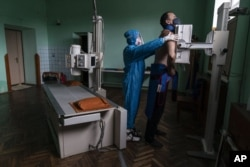 A medic prepares a coronavirus patient for a lung X-ray at a hospital in Stryi, Ukraine, Tuesday, Sept. 29, 2020. (AP Photo/Evgeniy Maloletka)