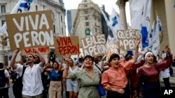 "FILE - Argentinian Peronists rally at the Plaza de Mayo with cardboard posters reading in Spanish; ""Long live Peron,"" ""Loyal to Peron,"" ""We love Peron,"" marking Peronist Loyalty Day, in Buenos Aires, Argentina, Oct. 17, 2013."