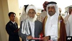 Naibu waziri wa mambo ya nje wa Qatari Ali bin Fahd al-Hajri na Jan Mohammad Madani, mmoja wa maafisa wa Taliban akikata utepe katika ufunguzi rasmi wa ofisi y aTaliban huko Doha, Qatar, June 18, 2013.
