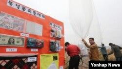 8일 군사분계선 근교 마을에서 대북전단과 생필품을 날려보내는 한국 민간단체 회원들.