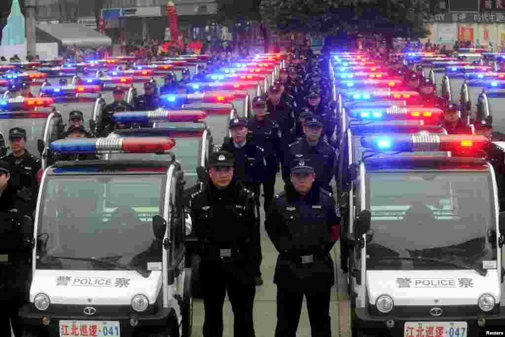 People watch a police force showcase during the debut of new patrolling police vehicles in Chongqing Municipality, China.