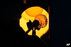 A glass-worker heats a glass artistic creation in a methane powered oven in Murano island, Venice, Italy, Oct. 7, 2021.
