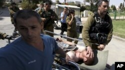 An injured Israeli soldier is wheeled into Soroka hospital in the southern town of Beersheva, Israel, following an exchange of fire with militants along Israel's southern border with Egypt, September 21, 2012.