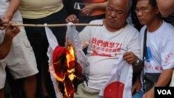 示威者在日本駐香港總領事館門外,焚燒象徵日本軍國主義的旗幟及標語