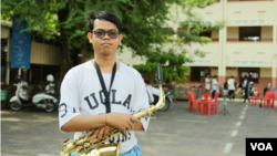 Otdom Praseth, a senior member of the Phnom Penh Marching Band, stands with his saxophone during a rehearsal at Kolab Primary School in Phnom Penh on October 7, 2018. (Rithy Odom/VOA Khmer)