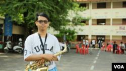 ឧត្តម ប្រាសិត កំពុងកាន់ឧបករណ៍ Saxophone។ (រិទ្ធី ឧត្តម/VOA)