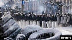 Polisi berjaga-jaga di tempat bentrokan dengan para demonstran anti-pemerintah di Kyiv (24/1).