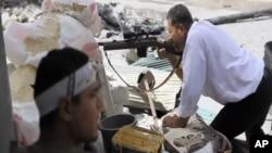 叙利亚自由军的一名战士在阿勒颇向政府军开火,另一名战士在掩体内