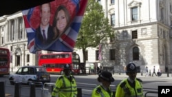 Police walk past a flag hanging outside a coffee shop, depicting Britain's Prince William and Kate Middleton, in Whitehall, in central London, April 27, 2011
