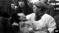 "FILE - A woman holds a victim of ""Minamata Disease,"" or mercury poisoning, in Minamata, Japan, in a1973 photo. The Minamata Convention, a global treaty aimed at curtailing the mining and use of mercury, took effect Wednesday."