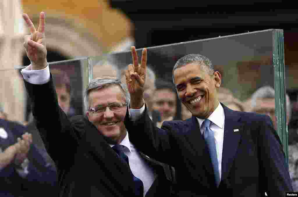 U.S. President Barack Obama and Polish President Bronislaw Komorowski show the peace sign at a Freedom Day event at Royal Square in Warsaw, June 4, 2014.