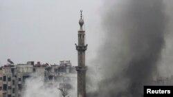 Asap hitam mengepul dari sebuah mesjid dan beberapa gedung saat berlangsungnya pertempuran antara pemberontak dan pasukan pemerintah pendukung Presiden Bashar al-Assad di wilayah Jobar, Damaskus, 6 Februari 2013. (REUTERS/Mohamed Dimashkia).