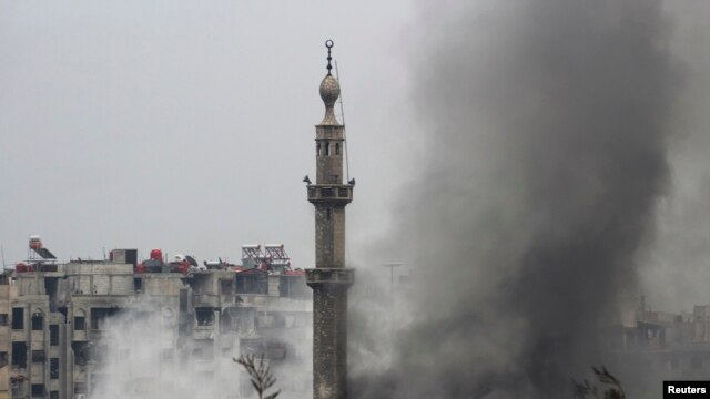 Smoke rises from a mosque and another building during heavy fighting in the Jobar area of Damascus Feb. 6, 2013. (Reuters)