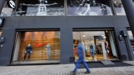FILE - A man walks past a Nike shop on Venice Street in Benghazi, Libya, Nov. 7, 2013.