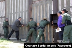 U.S. Customs and Border Patrol agents along with Rep. Juan Vargas open an emergency door at the U.S.-Mexico border in California during an event where immigrant families were able to spend three minutes together.