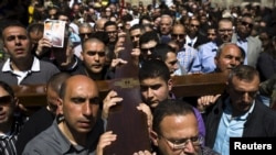 """基督教徒在耶稣受难日游行活动中搬运十字架走过耶路撒冷老城的""""苦难之路"""""""