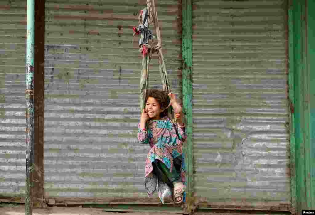A girl plays on a swing in Kabul, Afghanistan.