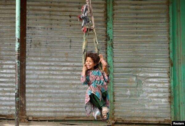아프가니스탄 카불에서 소녀가 그네를 타고 있다.