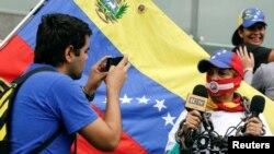រូបឯកសារ៖ បុរសម្នាក់ថតរូបស្រ្តីអ្នកយកព័ត៌មាន ដែលកំពុងរាយការណ៍អំពីការហែក្បួនប្រារព្ធពិធីទិវាសេរីភាពសារព័ត៌មានពិភពលោក នៅទីក្រុង Caracas ប្រទេស Venezuela កាលពីថ្ងៃទី៣ ខែឧសភា ឆ្នាំ២០១៦។
