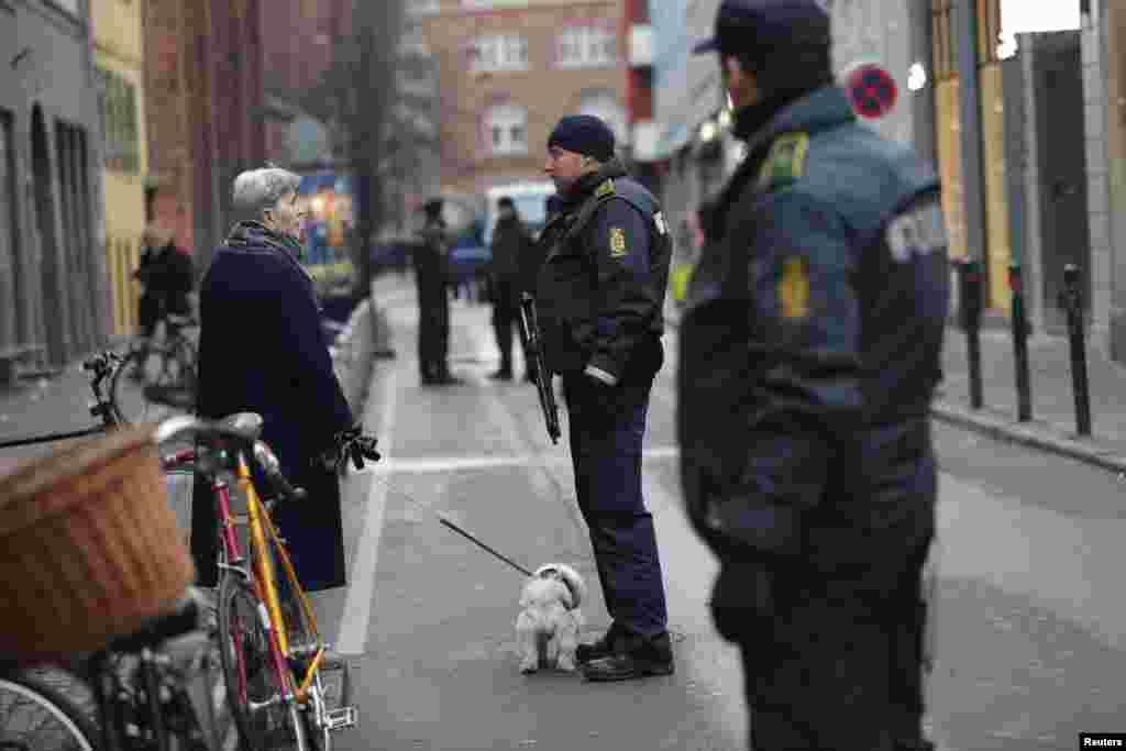 Seorang perempuan berbicara dengan polisi di depan sinagog di Krystalgade di Copenhagen, 15 Februari 2015.