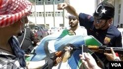 Pemberontak Libya merobek-robek poster pemimpin Libya Moammar Gaddafi di ibukota Tripoli (22/8).