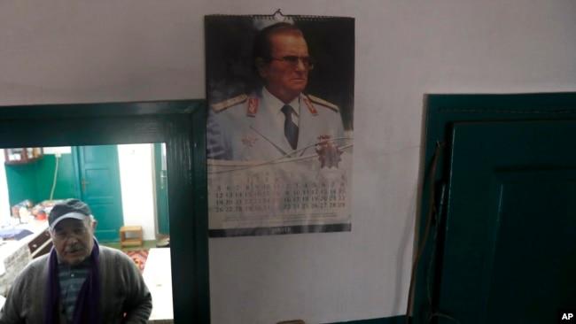 In this photo taken on Thursday, Jan. 23, 2020, Uros Trainovic walks inside his house decorated with picture of former Yugoslav communist president Josip Broz Tito, in the village of Blagojev Kamen, Serbia. (AP Photo/Darko Vojinovic)