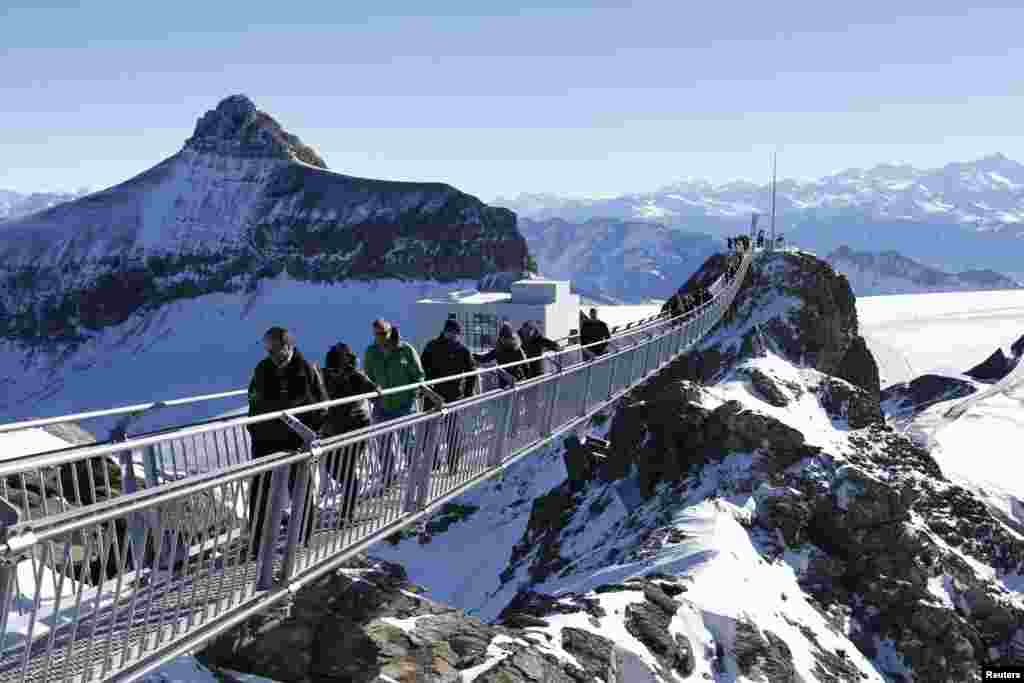 Guests walk along the 'Peak Walk' bridge during a media preview, at the Glacier 3000 in Les Diablerets, Switzerland. Built between the Scex Rouge and View Point at an altitude of 3,000 meters (9,800 feet) the 107 m (351 feet) long and 80 cm (31 inches) wide hanging bridge is the first in the world to connect two peaks with one another.