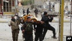 Irački vojnici i sunitski borci nose ranjenu ženu koju su pogodili pripadnici Islamske države.