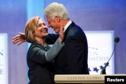 "FILE - Former U.S. President Bill Clinton and former U.S. Secretary of State Hillary Clinton embrace during the opening plenary session labeled ""Reimagining Impact"" at the Clinton Global Initiative 2014 in New York, Sept. 22, 2014."