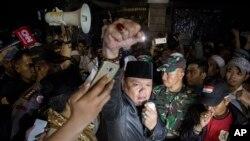 Seorang pemrotes mengangkat tinjunya dalam aksi demo anti-komunis di luar kantor Lembaga Bantuan Hukum Senin pagi, 18 September 2017. (AP Photo/Donal Husni)