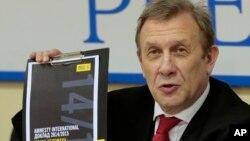 2015年2月24日國際特赦組織俄羅斯代表處主任謝爾蓋‧尼基京在新聞發佈會上出示國際特赦年度報告俄語副本。