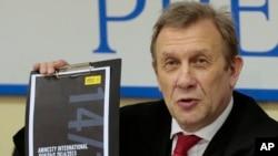 Giám đốc Văn phòng đại diện của Tổ chức Ân xá Quốc tế tại Nga cầm một bản sao phúc trình về nhân quyền năm 2014 trong cuộc họp báo tại Moscow, ngày 24/2/2015.
