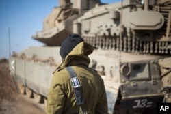 FILE - An Israeli soldier stands by a tank near the border with Syria in the Israeli-controlled Golan Heights, Nov. 28, 2016. Last month the BBC broadcast satellite images showing new buildings being erected 50 kilometers from Israeli installations on the Golan Heights. Iran is suspected of being behind the construction.