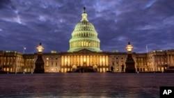 Lights shine inside the U.S. Capitol Building as night falls in Washington, Jan. 21, 2018.