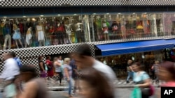 FILE - A photo taken with a slow shutter speed shows people walk through a shopping district in Sao Paulo, Brazil, Dec. 1, 2015. Brazil's finance minister said on Thursday that Congress has signaled its willingness to support tough measures to control spending.