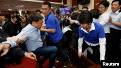 Ruling Democratic Progressive Party (DPP) legislator Chao Tien-lin, left, scuffles with opposition Kuomintang (KMT) legislators during budget meeting for the infrastructure development program, at the Legislative Yuan in Taipei, Taiwan, July 18, 2017.
