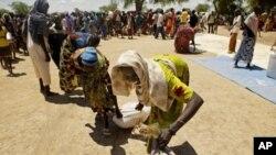 Refugiados sudaneses em busca de bagos de comida