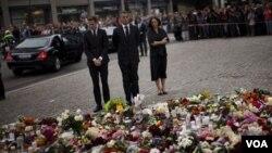 PM Jens Stoltenberg (tengah) memberi penghormatan bagi korban tewas dengan meletakkan karangan bunga di Oslo (24/7).
