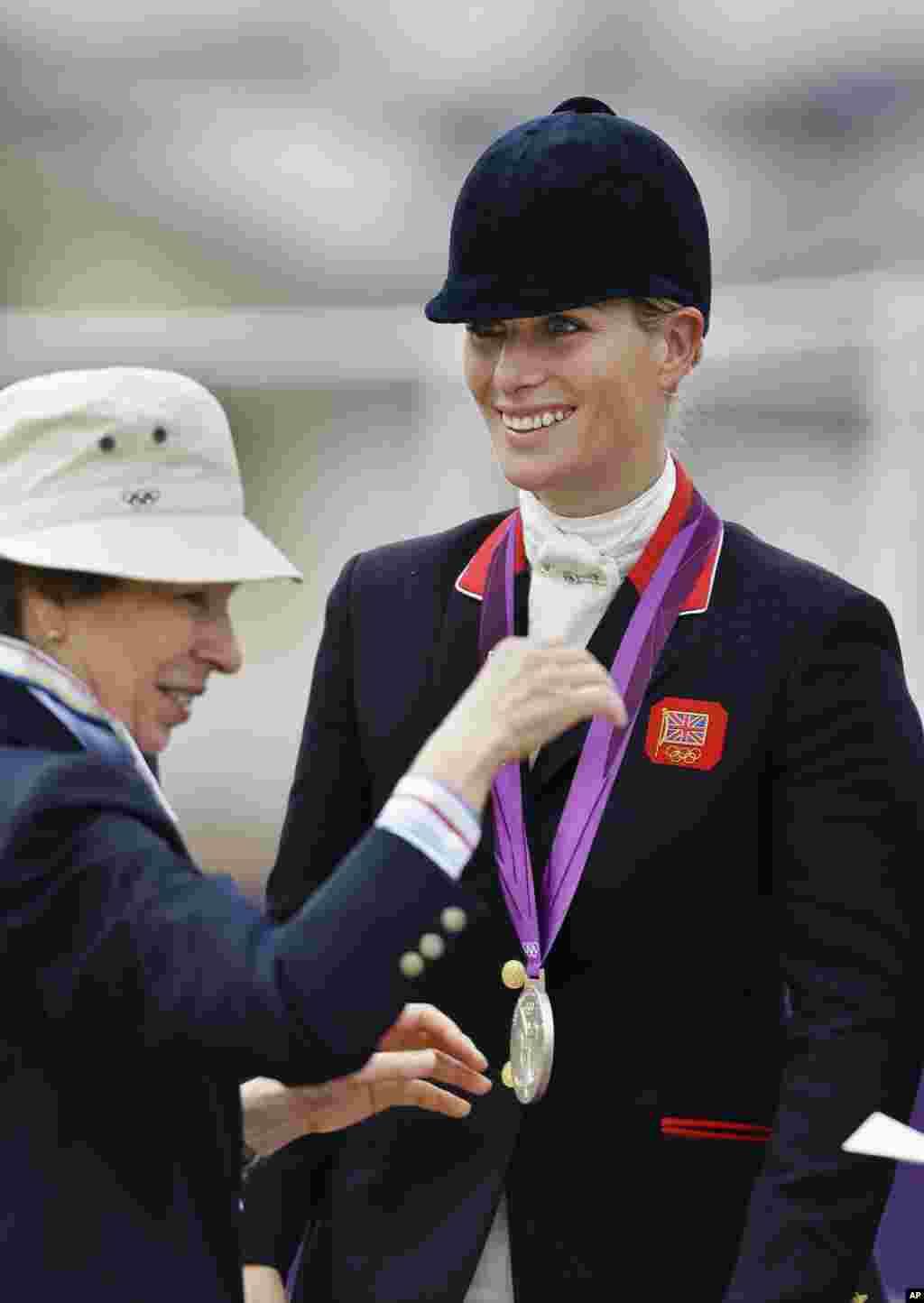 Внучка королевы Елизаветы Второй Зара Филлипс (справа) получает серебряную медаль из рук своей матери принцессы Анны