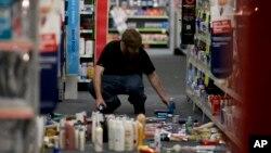 2014年3月28日晚,加州洛杉磯附近拉米拉達市一商店職工在收拾地震中散落的商品