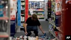 2014年3月28日晚,加州洛杉矶附近拉米拉达市一商店职工在收拾地震中散落的商品