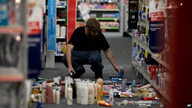 A man picks up fallen goods at a CVS store after an earthquake, March 28, 2014, in La Mirada, California.