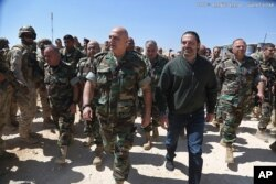 n this photo released by the Lebanese Army official website, Lebanese Prime Minister Saad Hariri, center right, walks with Lebanese Army Commander Gen. Joseph Aoun, center left, during a visit to the command center for the ongoing military operation agai