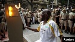 Obor Olimpiade dinyalakan oleh pembersih jalanan Renato Sorriso di pos pertama di Rio de Janeiro, Brasil Rabu (3/8).