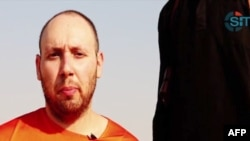 An image grab taken from a video released by the Islamic State (IS) and identified by private terrorism monitor SITE Intelligence Group purportedly shows U.S. freelance writer Steven Sotloff dressed in orange and on his knees in a desert landscape speaking to the camera before being beheaded by a masked militant (R), Sept. 2, 2014.