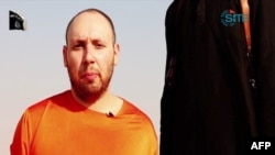 An image grab taken from a video released by the Islamic State (IS) and identified by private terrorism monitor SITE Intelligence Group purportedly shows U.S. freelance writer Steven Sotloff dressed in orange and on his knees in a desert landscape speaking to the camera before being beheaded by a masked militant (R).