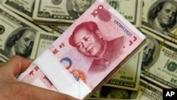 FILE - A pack of bills of Chinese yuan next to the U.S. currency. China pushes for yuan to be global currency, April 5. 2012.