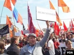 """在2012年5月6日普京就职总统前的莫斯科大规模反政府示威上,一名抗议者手举标语,""""普京是非法总统""""(美国之音白桦拍摄)"""